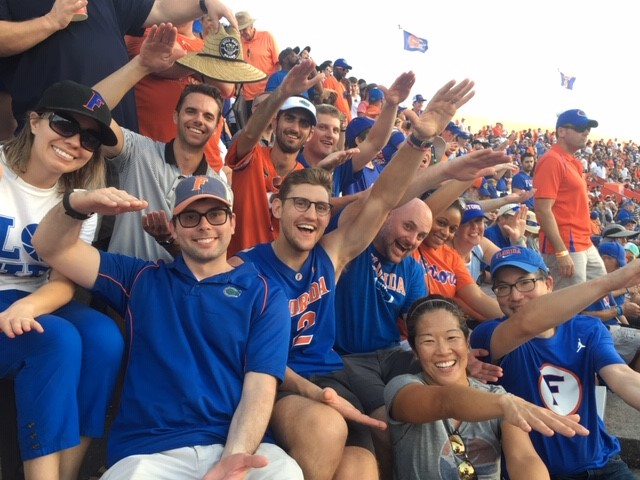 faculty and residents in the stands at the florida gators football game. all are smiling. all are doing the gator chomp