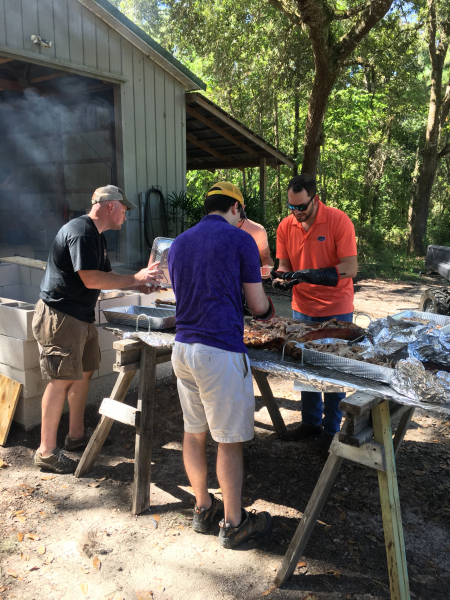 Photo of three residents and one faculty member cleaning the bar-b-que meat off the bones for the department gathering