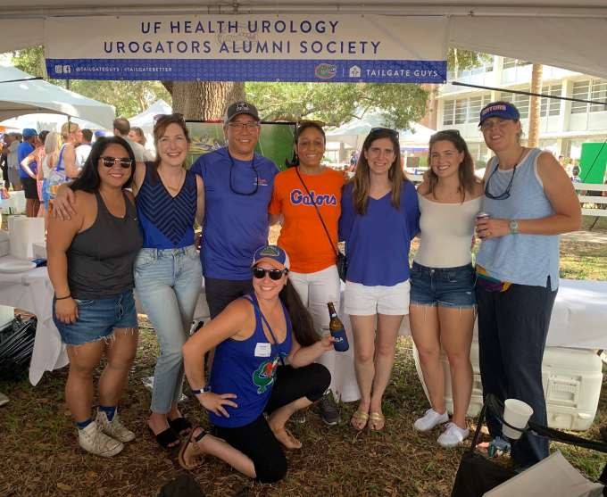 doctor su and some of the uf urology extenders.  they are standing under the urogators tailgate tent.  all are in shorts and tshirts.  they are standing arm and arm and all are smiling.