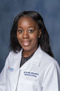 Star Dix is an aprn.  she is wearing a white doctors coat.  she has on a dark shirt.   she is in her late 20's.  she is African American.  she has long dark hair.  the background of the photo is medium blue.