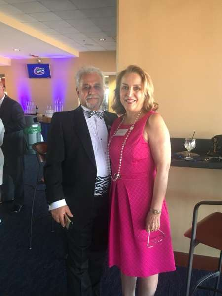 Doctor Vafa and his wife Doctor Zarandy. They are attending the 2018 Urology Resident Graduatiion Celebration. He is wearing a black tux with white shirt and black and white cumberbund and bowtie. He has grey and black hair with a mustache and goatee. She is wearing a hot pink dress with long strand of pearls holding her reading glases in her hand. She has shoulder length blonde hair. They both have happy smiles.