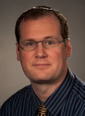 dr gideon richards in a blue and grey shirt.  he is wearing glasses