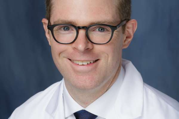 This photo is of Christopher E. Bayne who is a medical doctor. He is wearing his white lab coat with a white collared shirt and a dark blue tie. He has brown hair and is wearing black framed glasses. The background of the photo is medium blue.