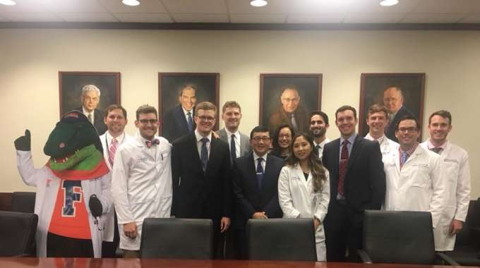 Doctor Nakada seated at a conference table. He is wearing a dark suite and tie.  He is surrounded by the UF Urology Residents. Some are wearing their white coats and some are wearing suits and ties  A cardboard cutout of Albert (the UF mascot) in a white doctors coat is also in the picture.