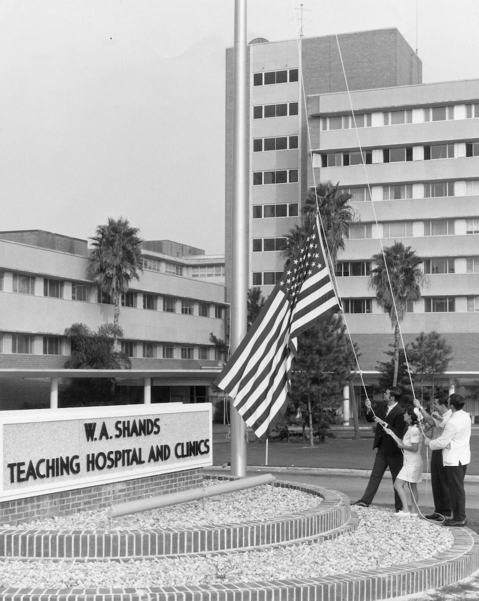 black and white picture of shands teaching hospital when it was first built in the early 40's. three people are helping to raise an american flag up a flagpole.