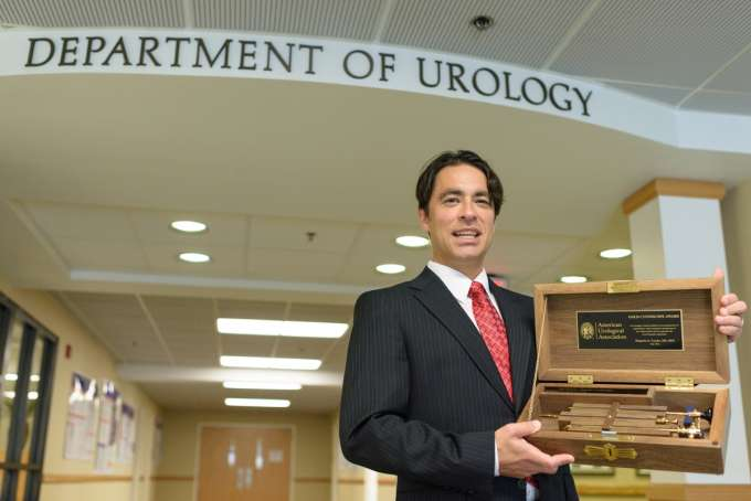 Doctor Canales is smiling and holding the gold cystoscope award.  It is a gold medical instrument in a wooden case.  He is wearing a dark suit with a white shirt and a red tie.  He is standing in front of the Department of Urology sign.