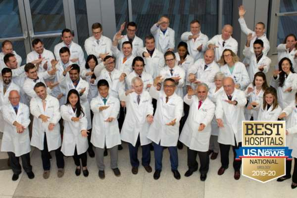 This is a large group photo consisting of Department of Urology Faculty, Residents and Extenders. In the photo is the U.S. News and World Report Best Hospital Badge for Urology 2019-20. Photo is taken from a point higher than those in the photo. They are doing the gator chomp.