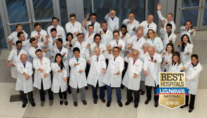 Group photo of the UF urology team. This includes faculty, residents and extenders. They are standing in multiple rows. They are all wearing their white doctor coats. They are standing in front the fountain at the UF Health Shands Cancer hospital. In the bottom right corner is the US News and World Report badge. This badge is gold with a blue banner across it with the words Best Hospitals US News & World Report National Urology 2019 - 2020.