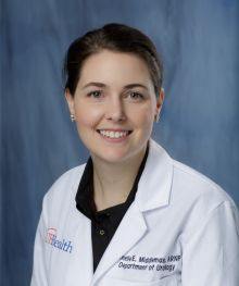 Amelie Middlemas, APRN  is wearing a white doctors coat.  she is wearing a black shirt.