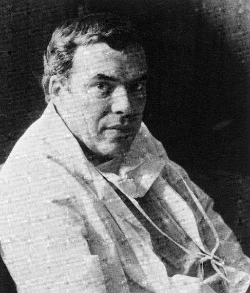 A black and white picture with Doctor Drylie in a white coat and a scrub mask hanging from his neck.