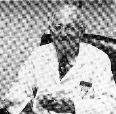 black and white picture of Doctor Grabstaldt sitting in a chair holding a manuscript.  he is wearing a white coat with items in the pocket.  he has on a shirt and tie.