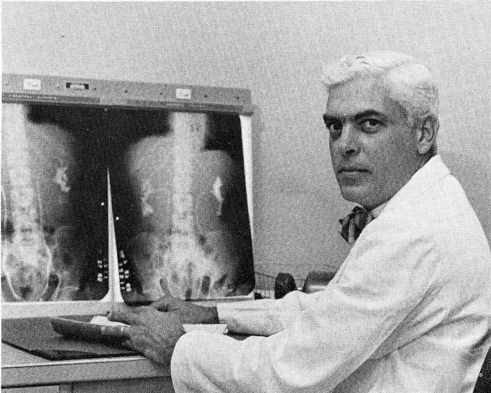 First Chief of Division of Urology Doctor George Miller.  He is in a white doctor coat looking at the camera with a xray scan in the background.