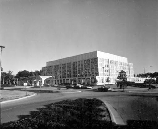 black and white picture of the Malcom Randall VAMC. the building is white with a portico in the front.  It has multiple floors.  There is a large circle drive in the front.