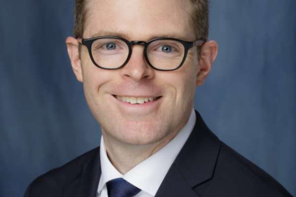 This photo is of Christopher E. Bayne who is a medical doctor. He is wearing a dark blue suit coat with a white collared shirt and a dark blue tie. He has brown hair and is wearing black framed glasses. The background of the photo is medium blue.