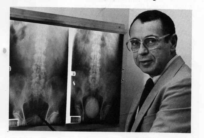 Doctor Wajsman is wearing a tan suit. He is looking at the camera with a xray in the background.
