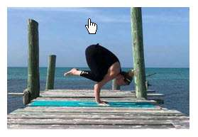 Jessica dressed in a black outfit with a black headband and is doing a yoga pose on a turquoise towel. Jessica is on a wooden pier with two wooden posts on left side an one wooden post on the right side of the pier. The pier is built out over a large water mass. Her yoga pose is a hand stand and she is resting on her knees on her upper arms holding herself up using her hands.