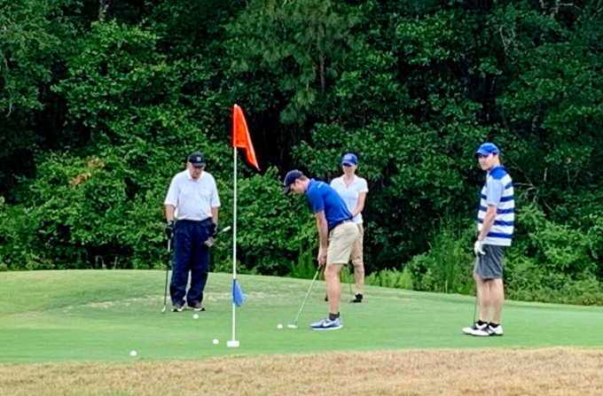 a green golf course with large green trees in the background. doctors dennis, domino and pavlinec are watching doctor stringer try to make a putt. they are wearing casual golf clothes.