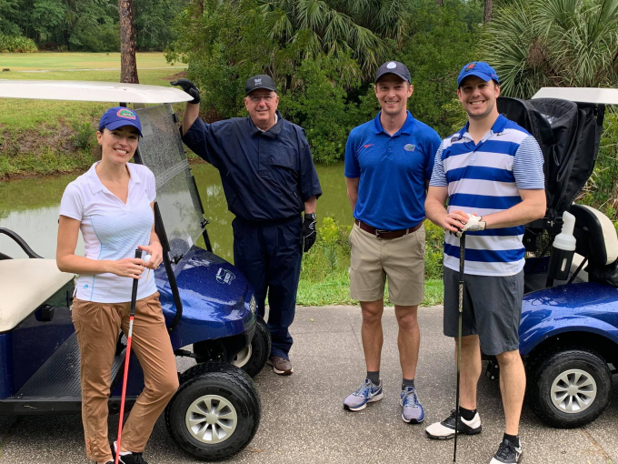 a golf cart on a golf path at ironwood golf course. doctor domino is standing near the cart, while doctors dennis, rabley and pavlinec are standing nearby. large green trees are shown in the background.