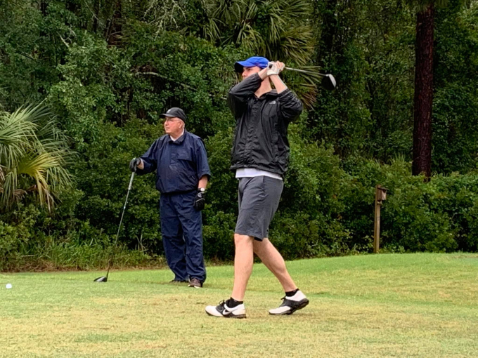 a green golf course with large green trees in the background. doctor pavlinec has just finished his shot. doctor dennis is leaning on his golf club watchiing.