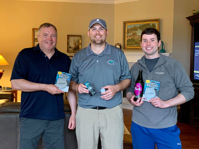 doctors crispen, archer and campbell showing their awards they won at the tournament. doctor crispen is holding a balzee. doctor archer isi holding a sleeve of golf balls and a singular golf ball. doctor campbell is holding a bottle of furki wine and a balzee. they are in the home of doctor tom stringer.