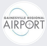 "the logo for the gainesville regional airport is a circle with a white background. the words gainesville regional is on the first line and airport is centered underneath. there is an airport symbol in the ""o"" o airport. A blue semi circle forms from the letter ""a"" in Gainesville to the ""r"" in regional. Another blue semi circle forms from the letter ""I"" in airport to the ""o"" in airport."