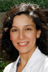 doctor muna canales' headshot. she is wearing a white doctors coat she has shoulder length dark hair.