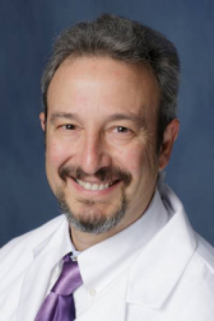 doctor donahoo is wearing a white doctors coat and a white button down shirt.  He has on a purple tie.  he has a mustache and gotee.