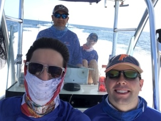 a beautiful day on the water at Cedar Key. Doctors Campbell and Galante are sitting down on a bench on the boat. Doctors Su and Domino are standing behind them. The water is a beautiful blue color with white wake waves behind it. the sky is a a clear blue.