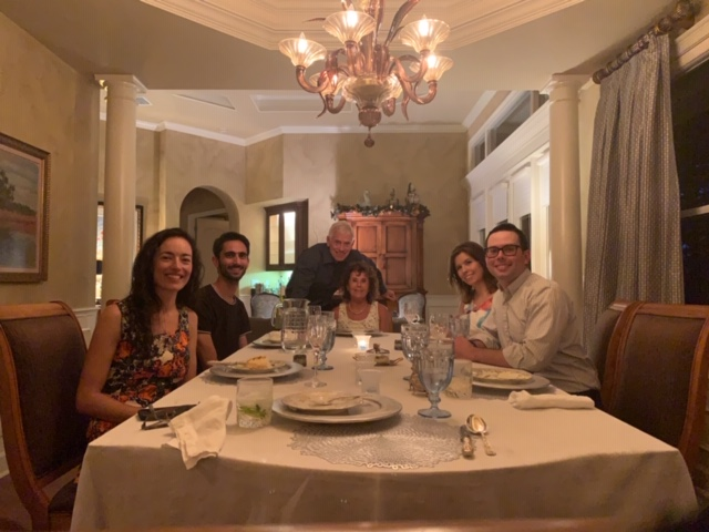 a group photo taken at the home of tom and leah stringer. doctors domino and galante are sitting on the left side of the dinng table. doctor stringer and his wife leah are sitting at the head of the table and doctor campbell and his wife danielle are sitting to the right. all are facing the camera. the dining room is spacious. all are dressed in business casual clothing. all are smiling