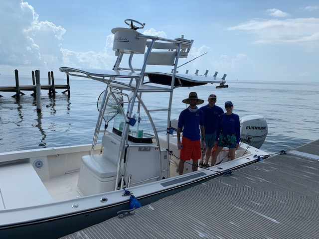 a beautiful day on the water at Cedar Key. Doctors Campbell, Domino and Galante are standing on a mid size white boat. the water is blue and the sky is blue with a few puffy white clouds. everyone is dressed in shorts, tshirts and hats.