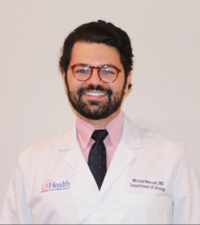 Doctor Michael Massari is a medical doctor and is wearing the white doctor coat, pink collared shirt and dark blue tie. He has short wavy black hair and is wearing round plastic glasses. He is standing in front of a white background