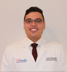 doctor merheb is wearing thie doctor coat, white collared shirt and black tie. he is standing in front of a white backgroun
