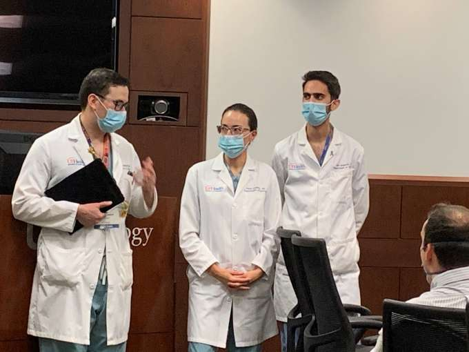 doctors campbell, domino and galante getting ready to present an award. all are wearing masks, scrubs and white doctors coats.