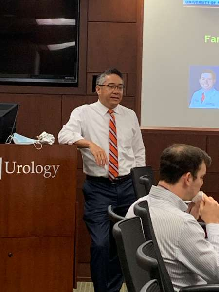 doctor su speaking the group. he is wearing dark pants, white collared shirt and an orange and blue tie. he is leaning with an elbow propped up on the podium in the conference room. it is dark wood in color and in silver polished lettering are the words UF Urology.