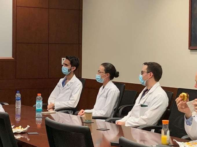 doctors galante, domino and campbell listeing to doctor su. all are wearing scrubs, white doctors coats and masks.