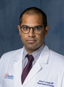 Headshot of Jason Joseph who is a medical doctor. He is wearing his white doctors coat with a purple and white small plaid shirt and a purple tie. He is wearing dark framed glasses. The background of the photo is blue.
