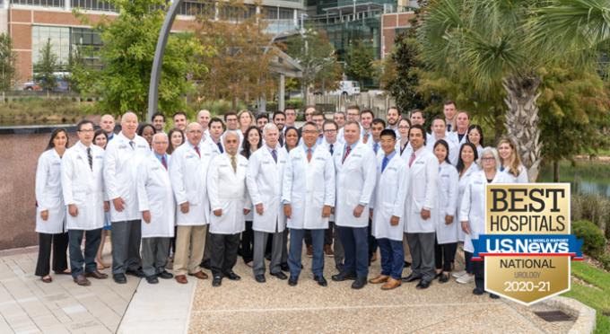 Group photo of the UF urology team. This includes faculty, residents and extenders. They are standing in multiple rows. They are all wearing their white doctor coats. They are standing in front the fountain at the UF Health Shands Cancer hospital. In the bottom right corner is the US News and World Report badge. This badge is gold with a blue banner across it with the words Best Hospitals US News & World Report National Urology 2020 - 2021.