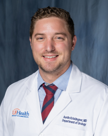 Doctor Austin Krishinger, who is a medical doctor, is wearing his white doctors coat with a blue collared shirt with a red and blue tie. the background of the photo is medium to dark blue.