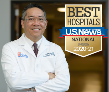 Doctor Li-Ming Su is wearing his white doctor coat. He is standing with his arms folded across his chest. He is smiling. He is wearing a white shirt and a patterned tie. He is wearing glasses with a clear frame. he is standing in front of the department of urology sign located in the UF Health Shands Hospital North tower. This is the location of the administrative offices.