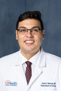 Doctor Merheb, , is wearing his white doctors coat with a white collared shirt with a red tie with small blue designs.  the background of the photo is medium to dark blue.