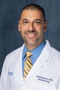 David is wearing a white doctors coat with a blue collared shirt and yellow and blue striped tie.