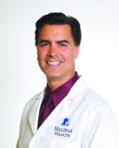 PICTURE OF DOCTOR BENNETT SCAGLIA. HE IS WEARING A WHITE DOCTORS COAT WITH A DARK PURPLE SHIRT AND TIE. THE BACKGROUND OF THE PHOTO IS WHITE.