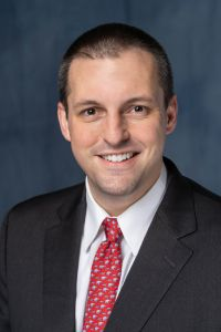 Professional photo of doctor russell terry. he is wearing a dark suit with a white collared shirt and red tie.