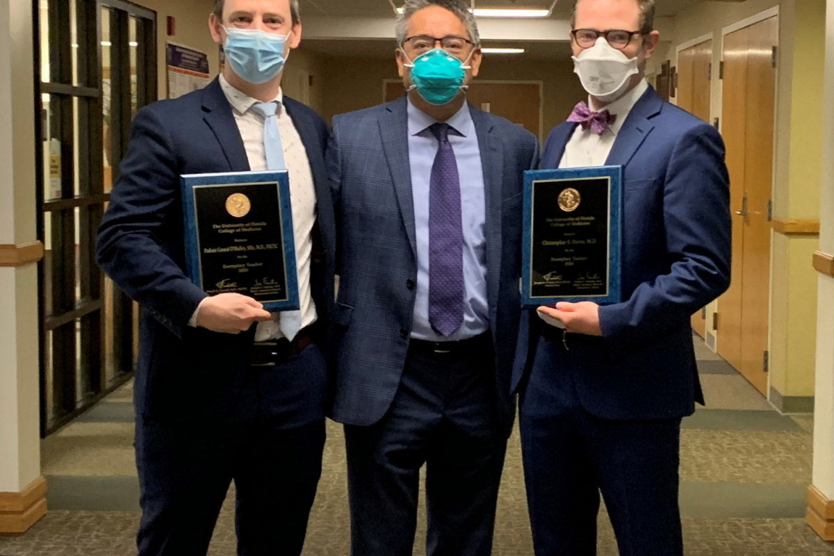 doctors o'malley, su and bayne are pictured in the office of chairman doctor su. they are all wearing blue suits. doctor o'malley (on the left) is wearing a white collared shirt with a light blue tie. doctor su (center) is wearing light purple collared shirt and a purple tie. doctor bayne (on the right) is wearing a white collared shirt and orange and blue bow tie. doctors o'malley and bayne are holding their awards. they are all 3 wearing face masks.