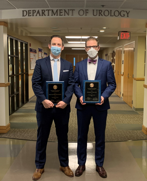 doctors o'malley and bayne are pictured in the hallway of the department of urology under the department of urology sign.  they are both wearing dark blue suits with white shirts.  doctor o'malley is on the left and he is wearing a white collared shirt with a light blue tie.  doctor bayne is on the right and he is wearing a white collared shirt with n orange and blue bow tie.  they are each holding their award and are both wearing masks.