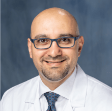 doctor mansour has on white collared shirt with a blue patterned tie. he has a white doctors coat.