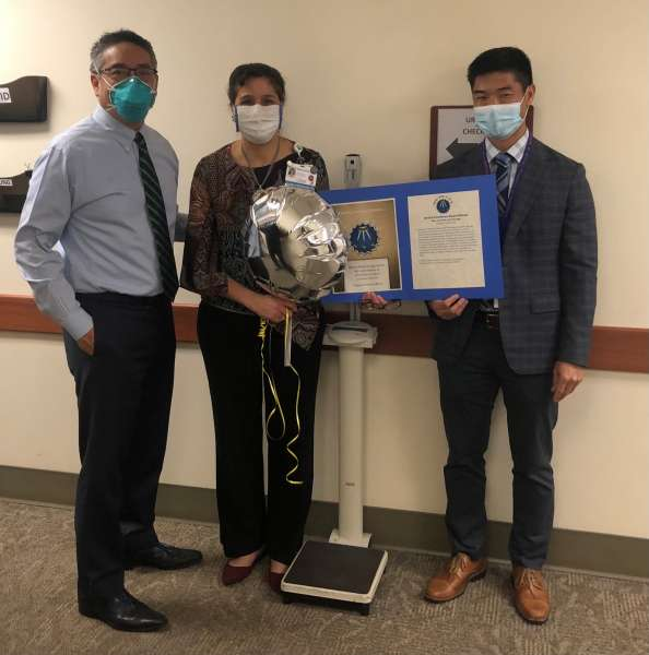 pictured left to right are doctor li-ming su, rhea carnevale and doctor larry yeung.  they are all dressed in professional attire.  they are all wearing masks.  Rhea is holding a silver balloon and a certificate.