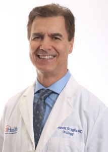 PICTURE OF DOCTOR BENNETT SCAGLIA. HE IS WEARING A WHITE DOCTORS COAT WITH A BLUE HIRT AND GRAY BLUE TIE.