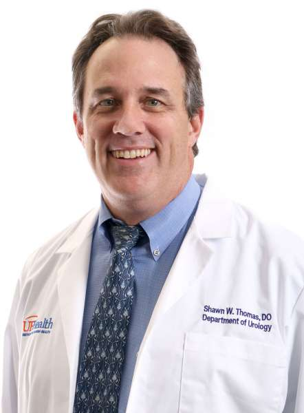 PICTURE OF DOCTOR SHAWN THOMAS.  HE IS WEARING A WHITE DOCTORS COAT WITH BLUE COLLARED SHIRT and blue tie