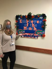 jennifer thompson is wearing a grey sweater and dark pants.  she is wearing  face mask.  She is standing in front of a sign that says employee of the month.  It is decorated in orange and blue.